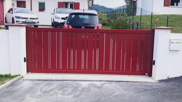 Portail coulissant motorisé en aluminium rouge basque installé par votre artisan à Hasparren